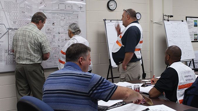 Responders in the Incident Command: Capabilities, Planning and Response Actions for All Hazards (IC) course review an area map as they plan the response to an incident.