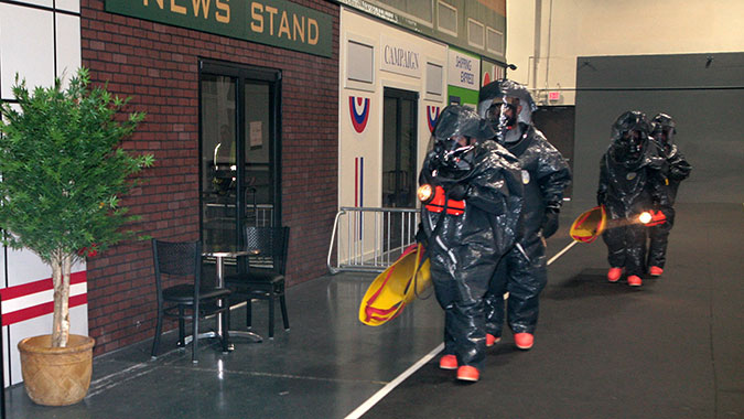 A group of emergency responders attending training at FEMA's Center for Domestic Preparedness (CDP) prepare to enter the CDP's mock subway train system through a simulated street scene used in training. These responders are part of the United States Army National Guard 140th Chemical Company from Lo