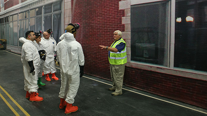HEC instructor David Blaker (right) explains the training scenario to five HEC students. During the scenario, the students applied the information they learned during the course regarding the collection of evidence in a hazardous environment.