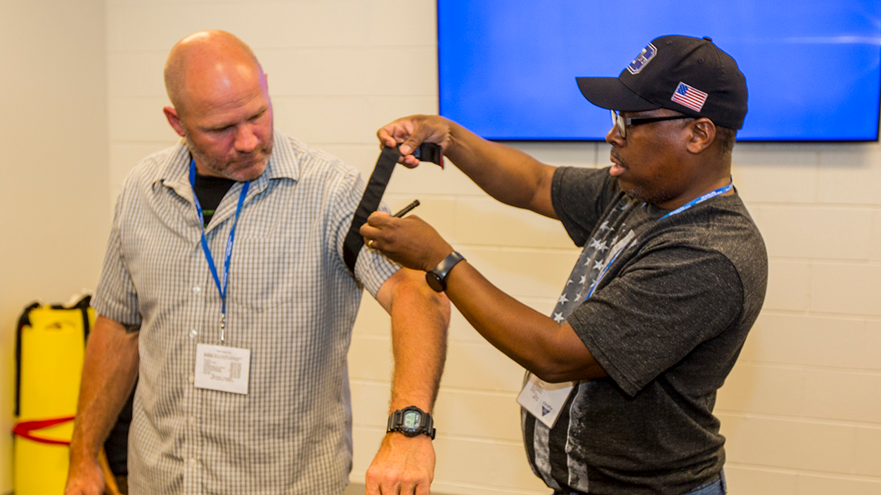 Instructor-in-training Winslow Harrison (right), an emergency medical technician, applies a tourniquet to the arm of a fellow student during the Instructor Training Course.