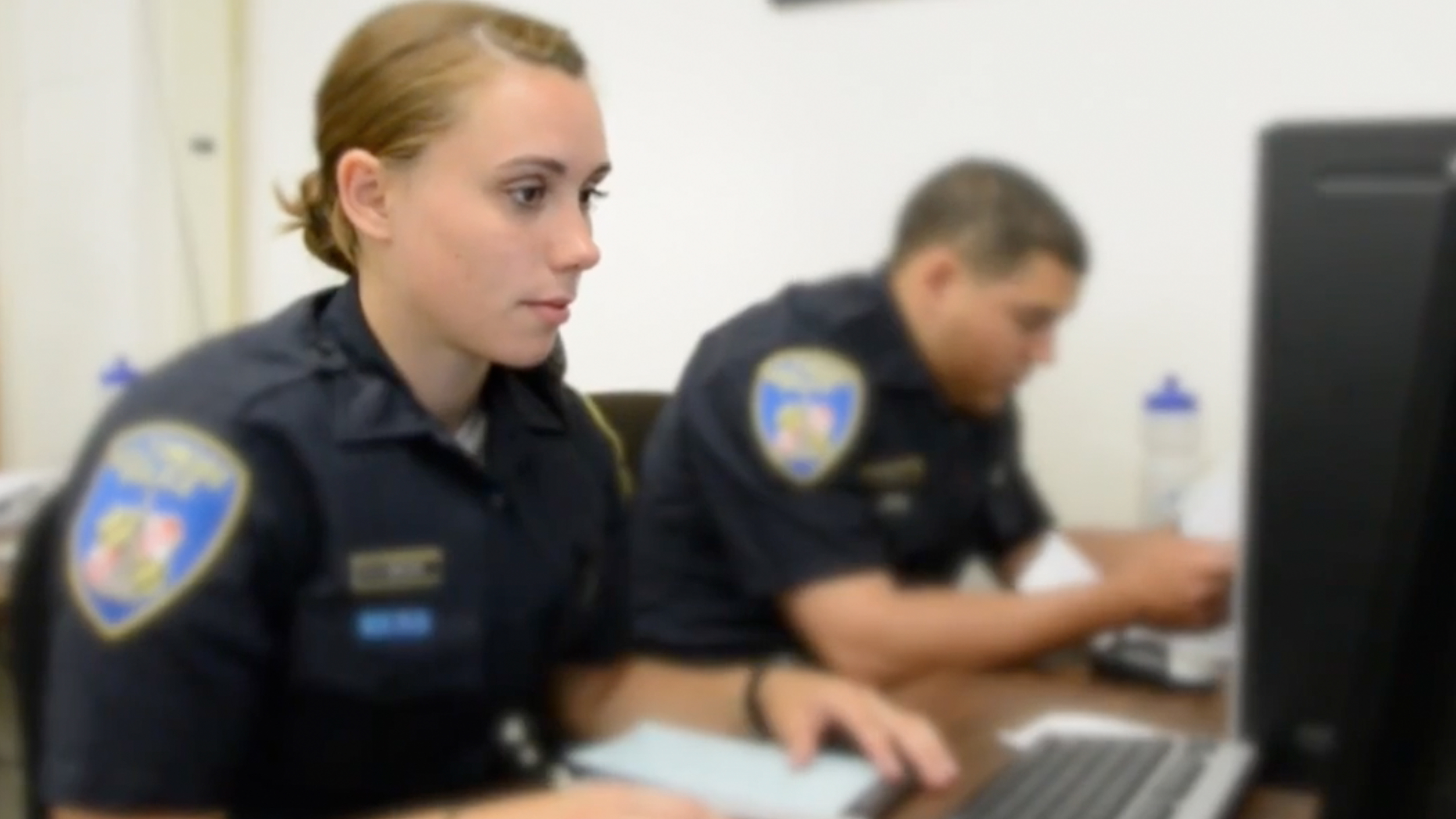 Police officers sitting at computers taking online training