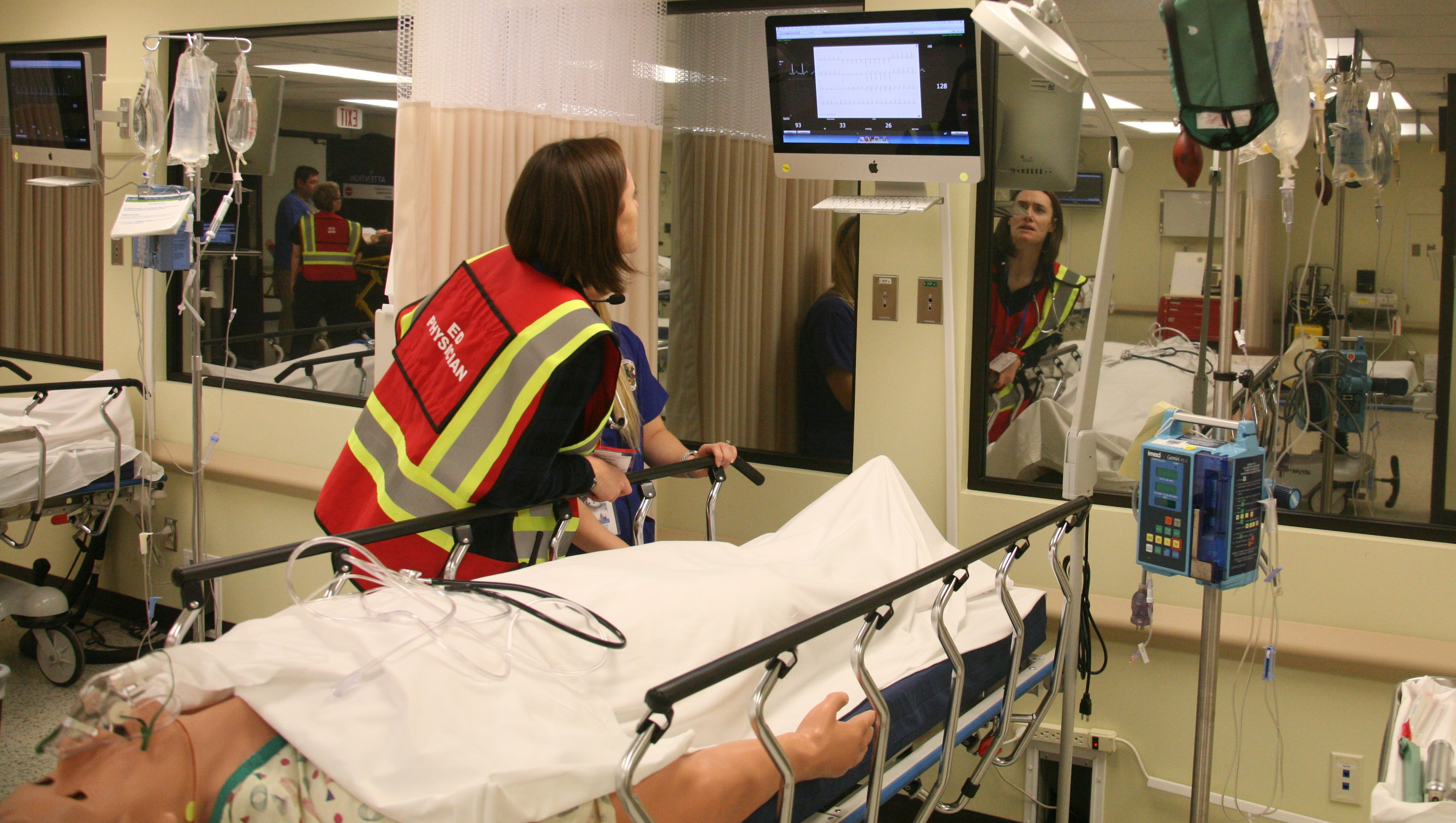 Student checking vitals of medical patient simulator in the emergency room during capstone mass casualty exercise.