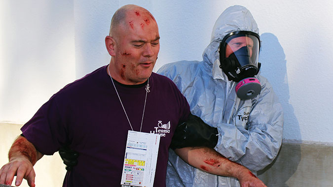 "A student in the Emergency Medical Operations for CBRNE Incidents (EMO) course escorts a ""survivor"" from the incident scene during the Integrated Capstone Event (ICE)."