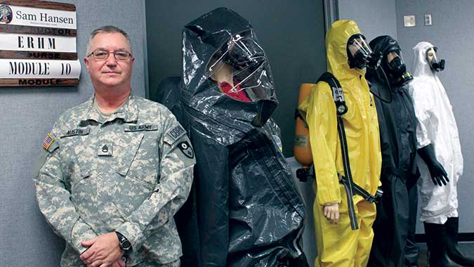 Staff Sgt. John Austin, of the 149th Chemical Company, takes a break alongside some of the personal protective equipment used in the ERHM course.